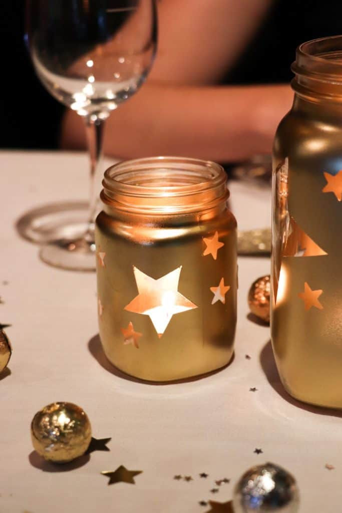 Gold jars with stars and tea light candles. Christmas table decor.