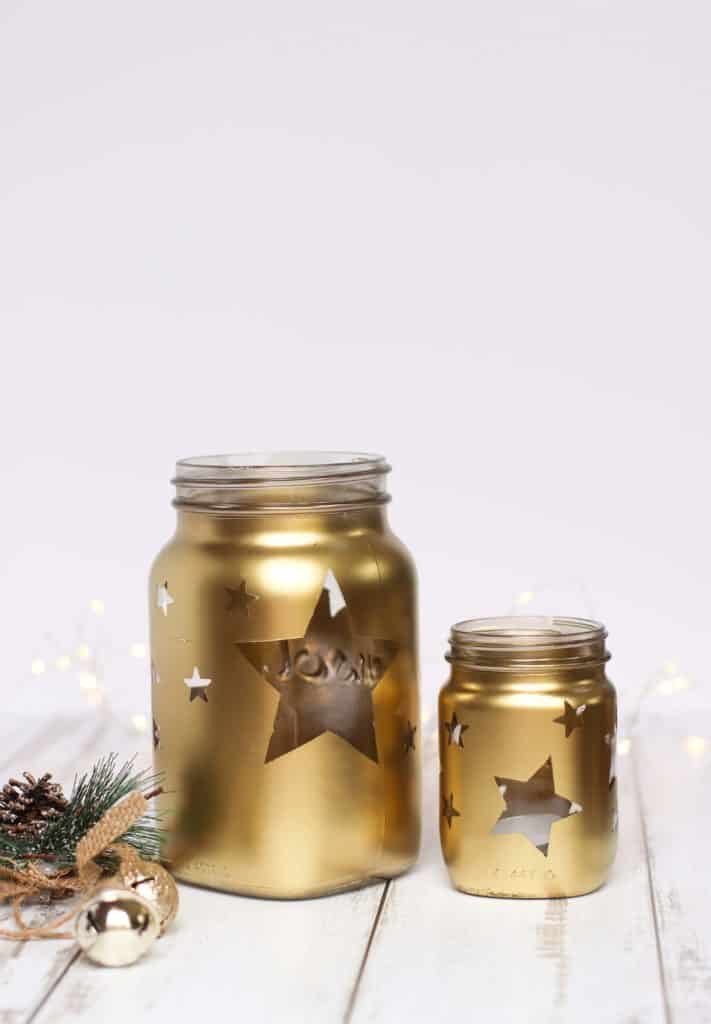 Gold jars with stars and tea light candles. Christmas decor.