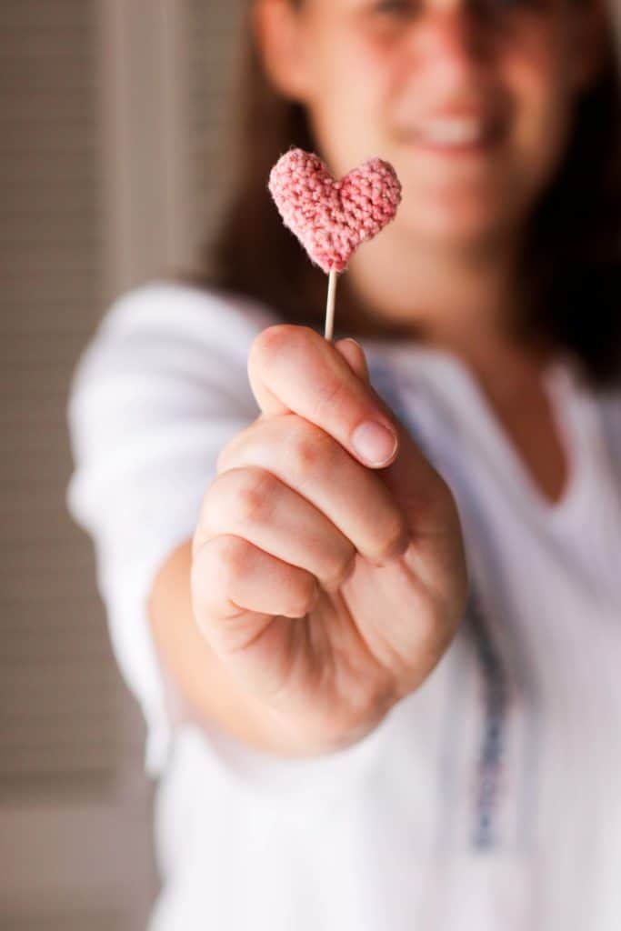 Woman holding a small pink crocheted heart on a stick