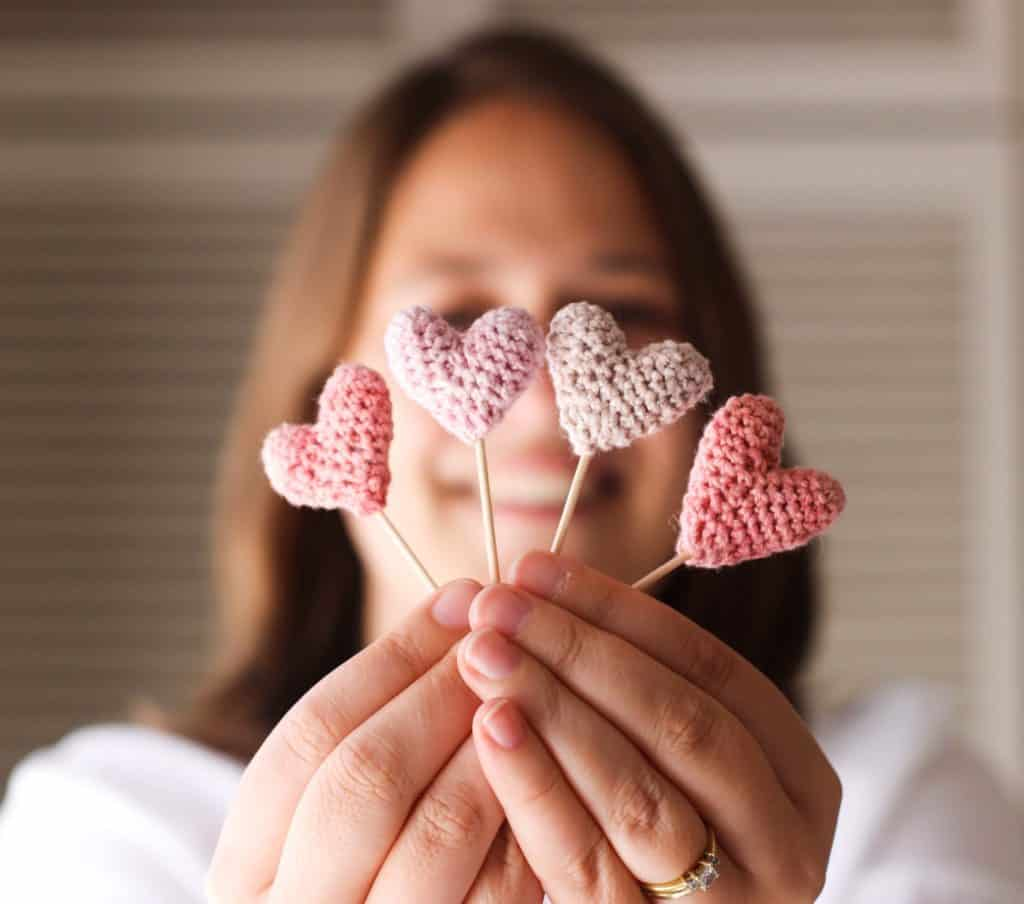 Lady holding four small crochet hearts in front of her