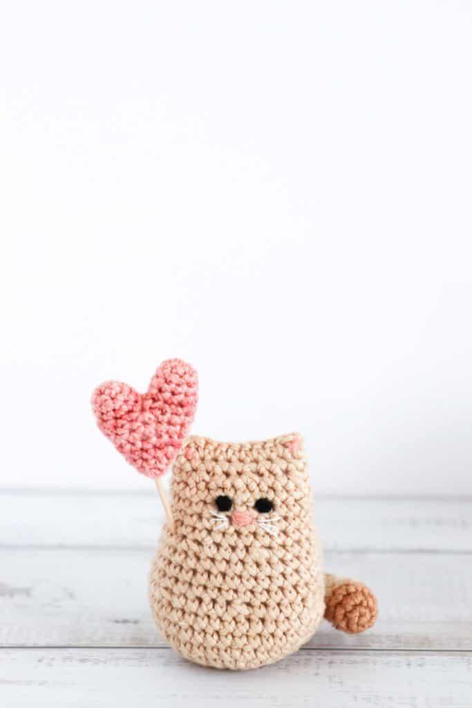 a crochet valentine cat with a pink crochet heart