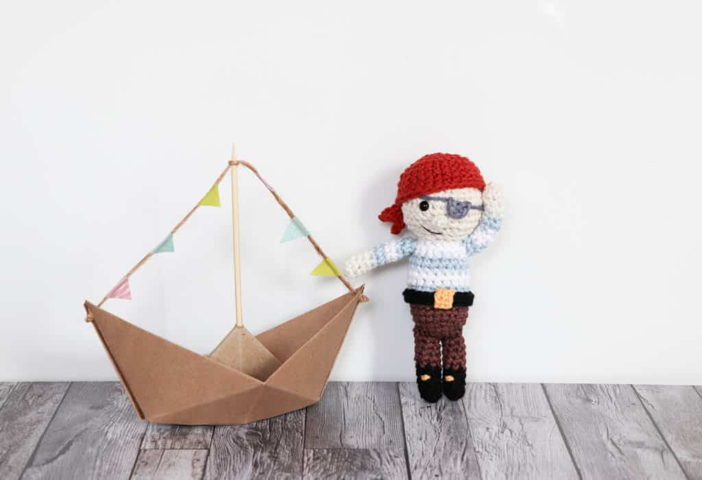 crochet pirate pattern | happy hand made crochet pirate standing next to a boat, pirate amigurumi, crochet gift for boys