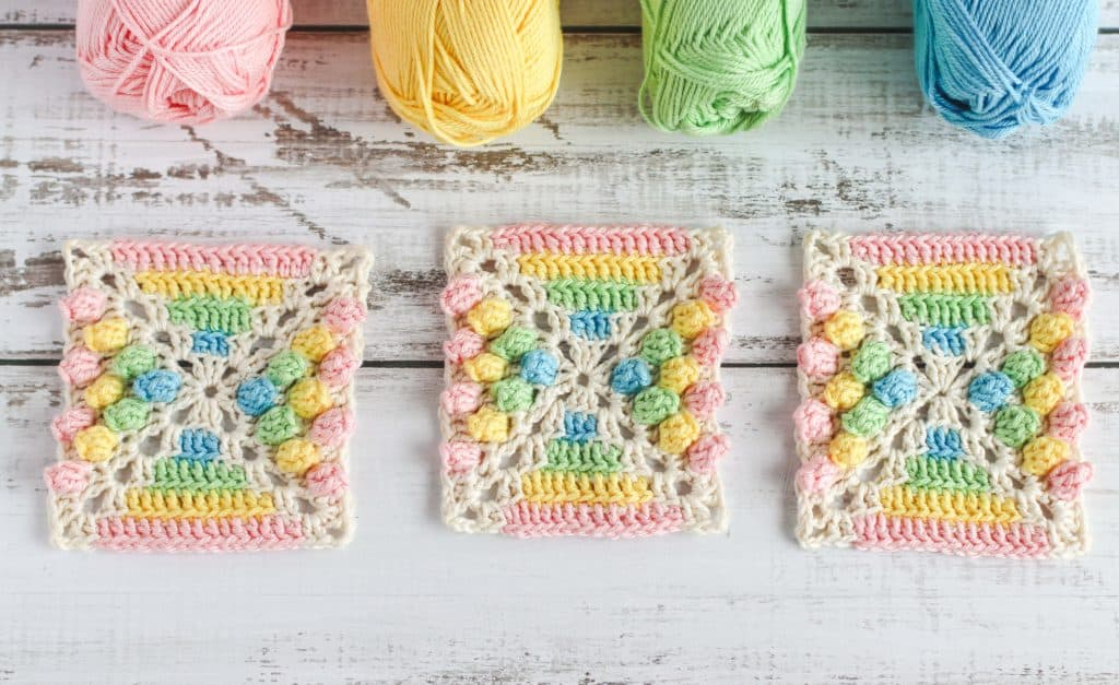 crocheted granny square in rainbow colors with puff stitches