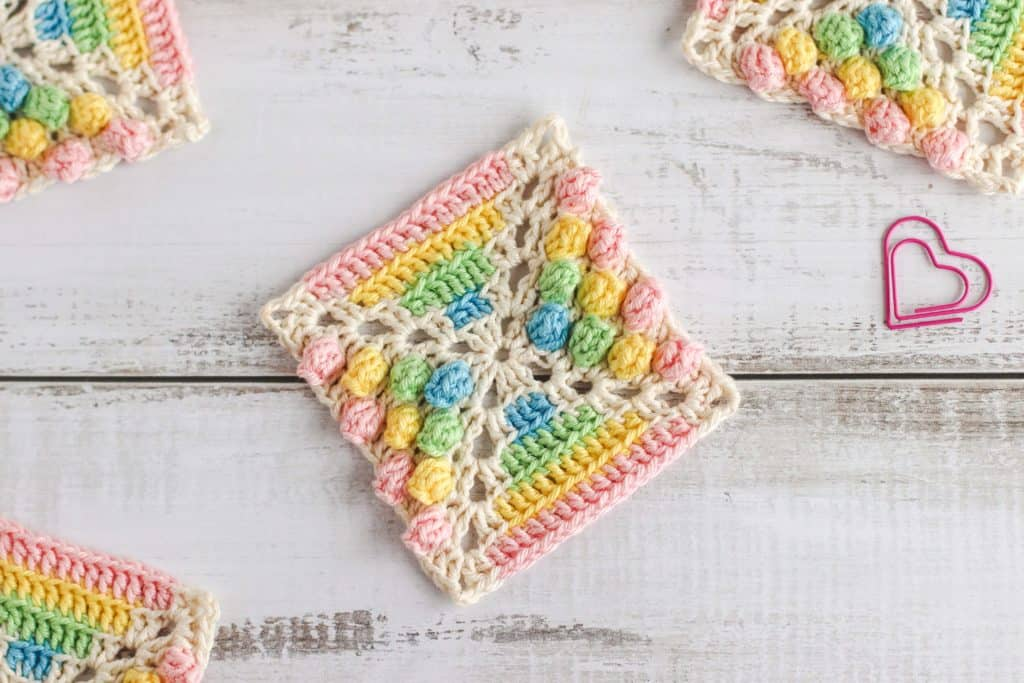 crocheted granny square using crochet cotton in pink, yellow, green, blue and cream