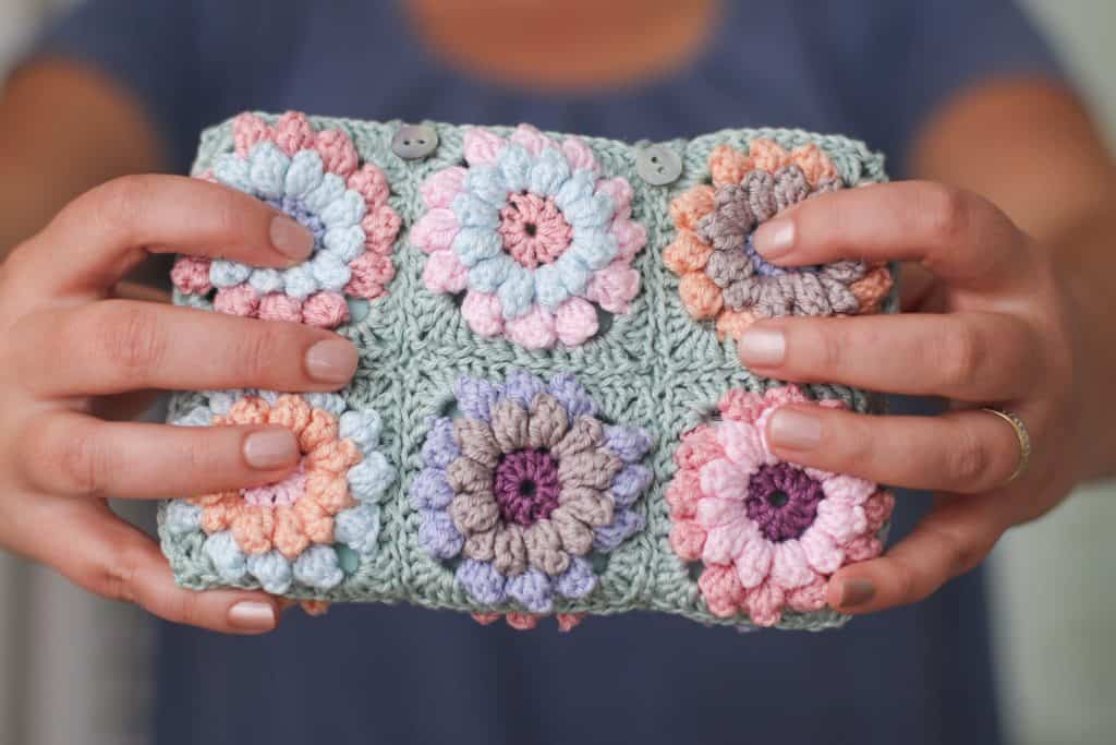 colorful crochet flower pouch, pink, purple, blue, green pouch held towards the camera