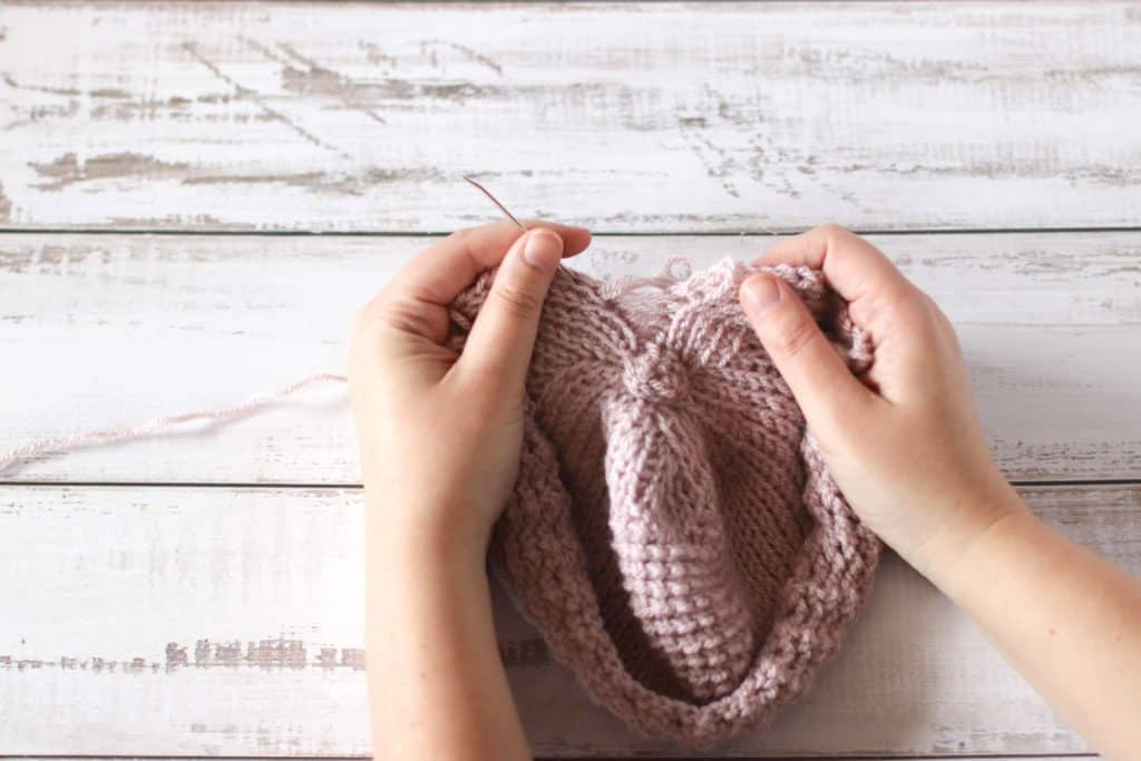 How to crochet a Tunisian crochet baby hat. Hands showing where to place a need in a crocheted hat.