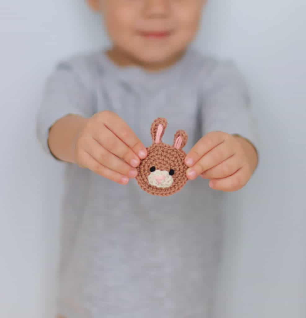 a brown crochet bunny applique held by a small boy, bunny applique crochet pattern