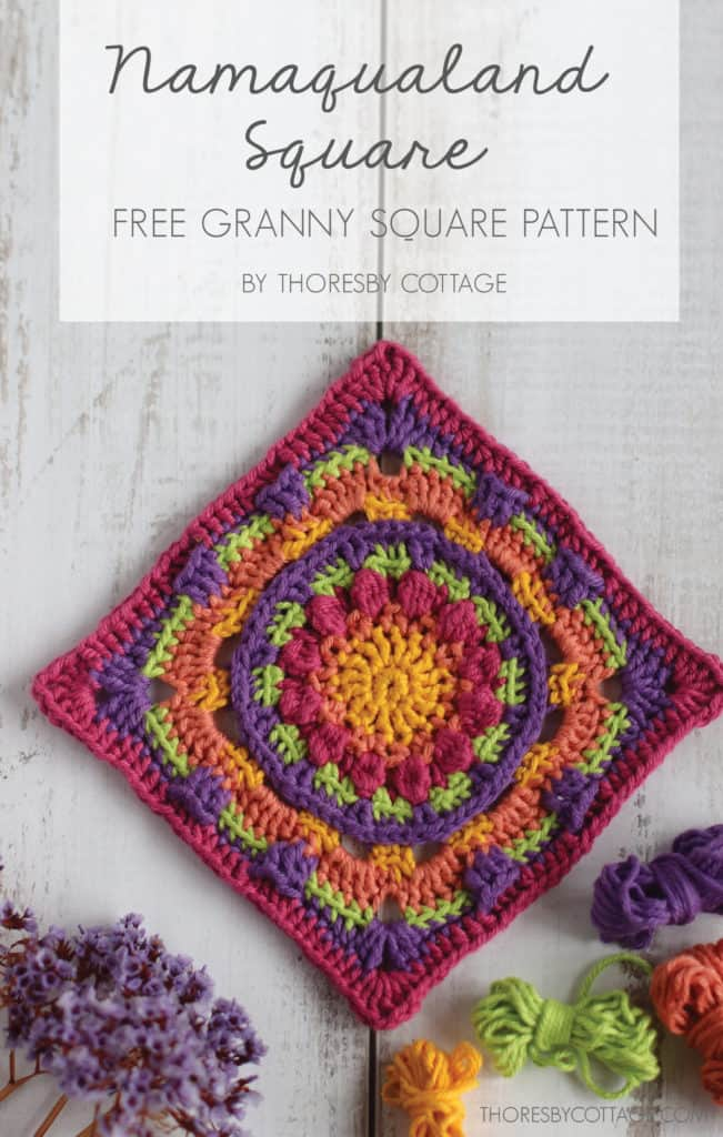 Brightly colored crochet granny square on a textured wooden background