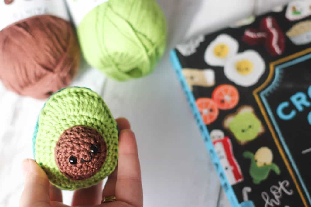 A crocheted avocado amigurumi with the crochet cafe book and brown and green yarn in the background.
