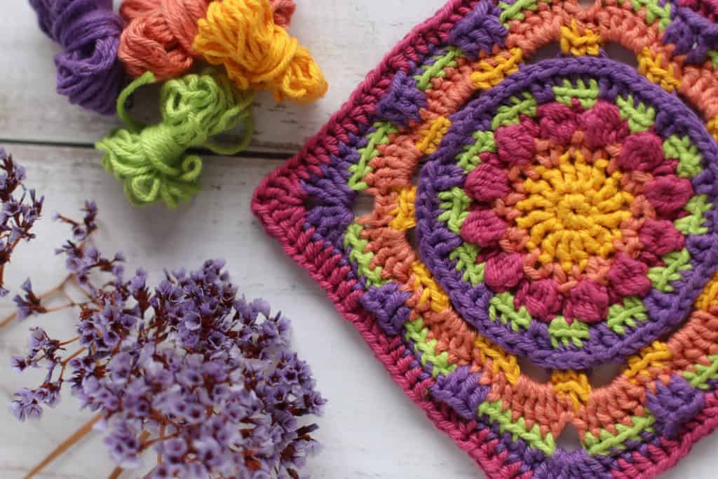 Brightly coloured crochet square, in orange, purple, pink and yellow