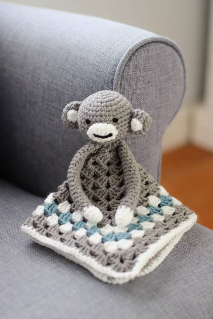 grey, blue and white crochet monkey lovey propped up on a chair