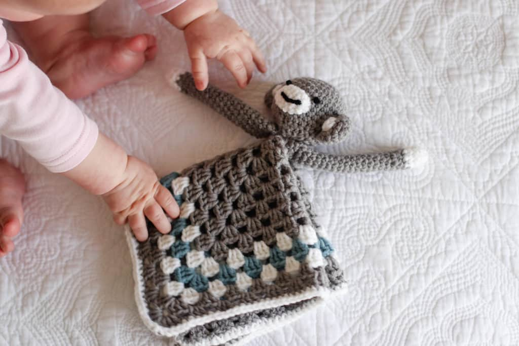 crochet monkey lovey that is being reached for by baby hands