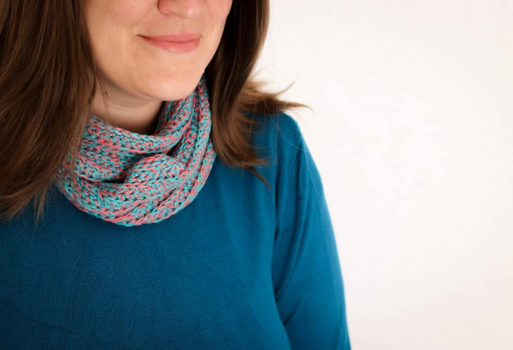 Close up of an crochet infinity scarf, in teal and watermelon