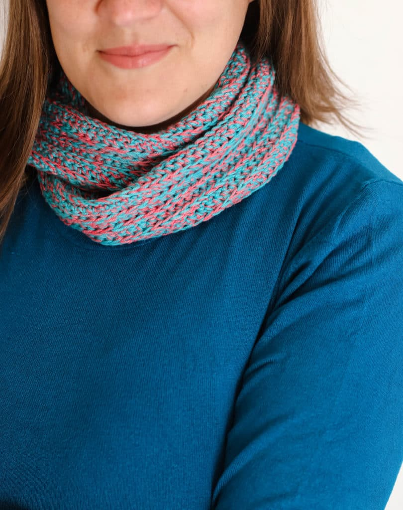 crochet infinity cowl or scarf in turquoise and watermelon on a teal background.