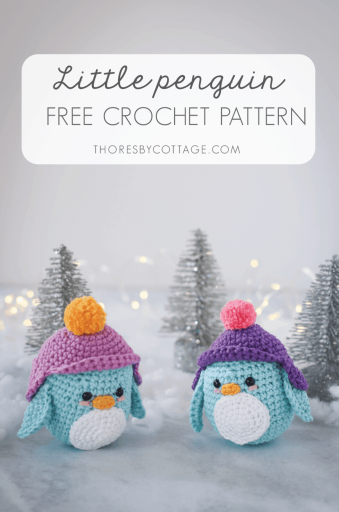 two blue crocheted penguins in a cold winter scene with glittery trees in the background