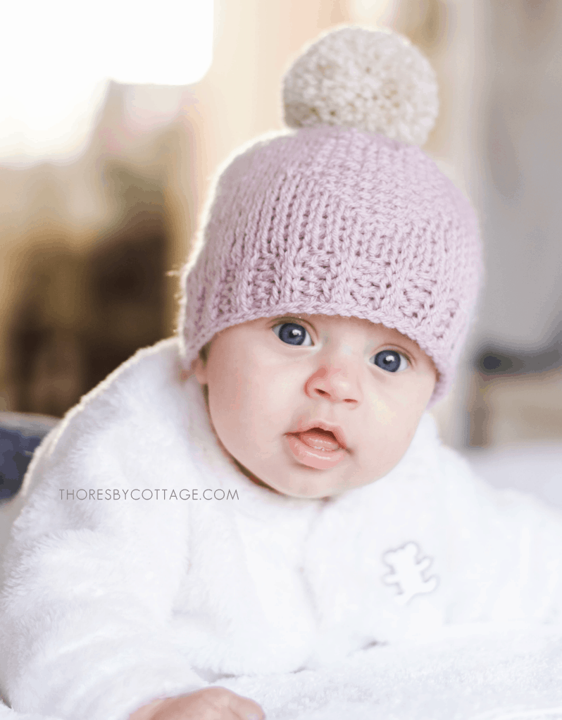 Blue eyes baby with a pink crocheted hat topped with a large pom pom