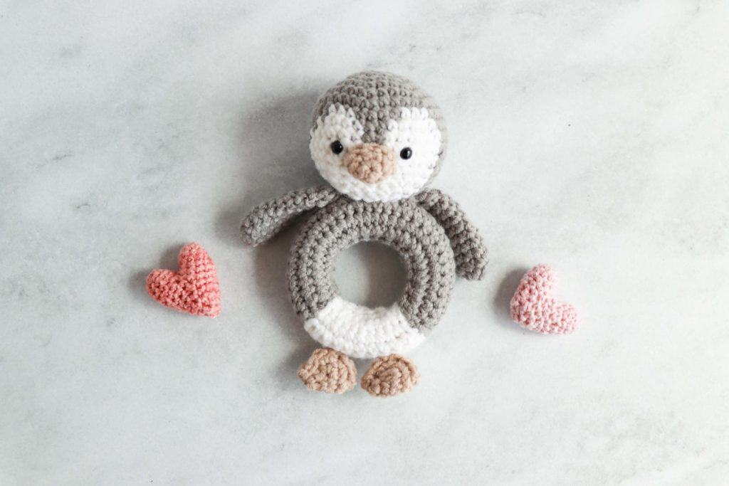 crochet penguin rattle flanked by two pink crochet hearts
