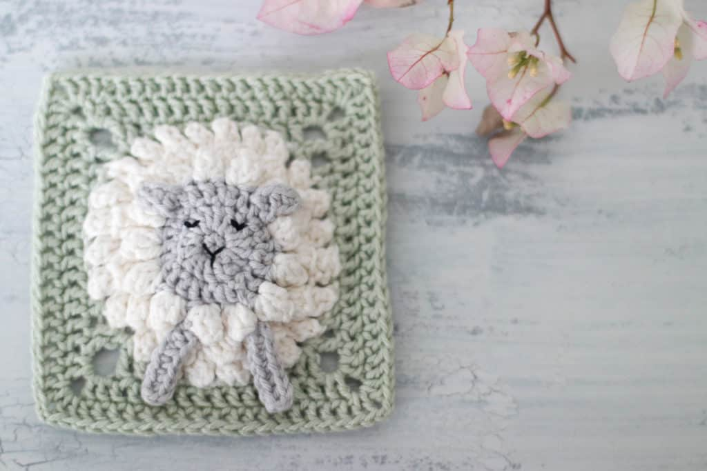 crocheted lamb square with pink flowers