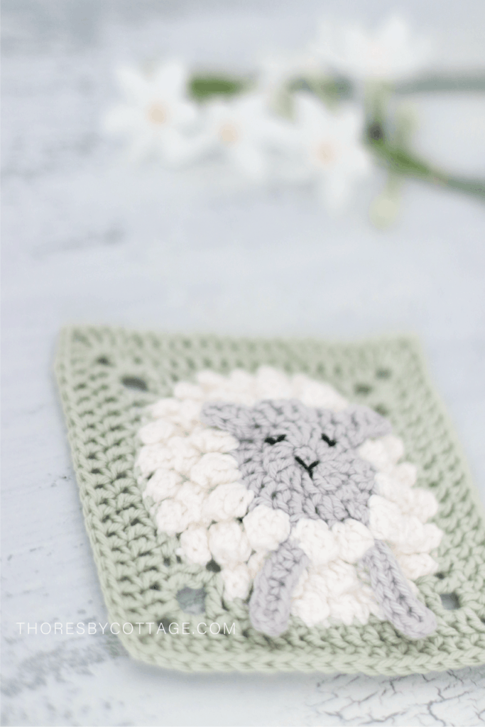 Fluffy white lamb, green crocheted square with flowers in the background.
